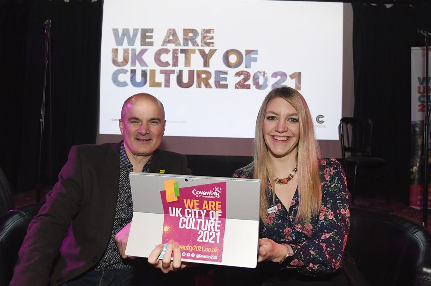 Alan Malik and Laura McMillan holding a laptop with a sign saying We Are UK City of Culture 2021 behind them