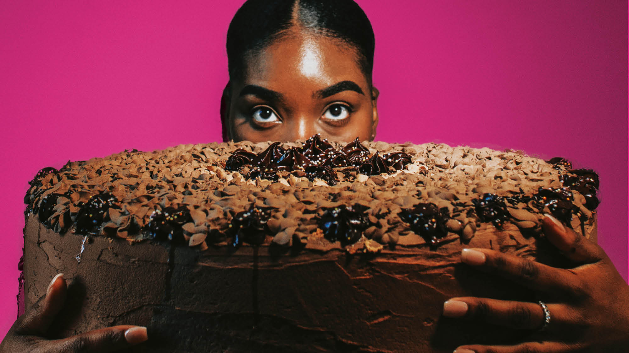 Image: Woman's head appears behind large cake in the foreground, hands wrapped around both sides. Solid pink background.