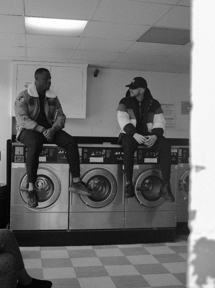 Image: Two men sitting on top of washing machines in a Coventry launderette. Image credit: HKD Media.