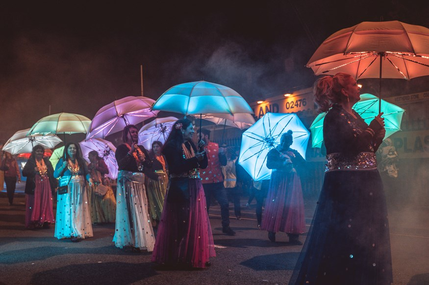 A line of women in brightly coloured, glittering Indian dresses holding colourful umbrellas lit up with LEDs at the 2019 Carnival of Lights