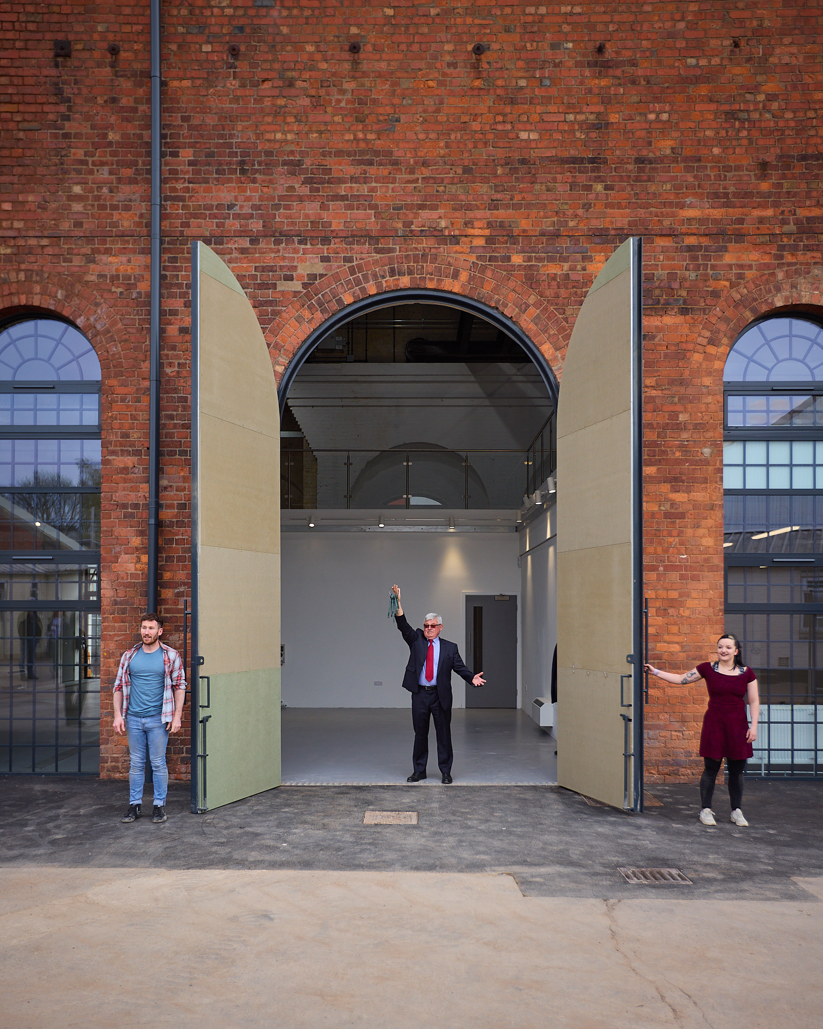 Roger Medwell stands in the open doorway of the new Daimler Powerhouse Creation centre with performers Luka Owen and Daniel Connor  on either side