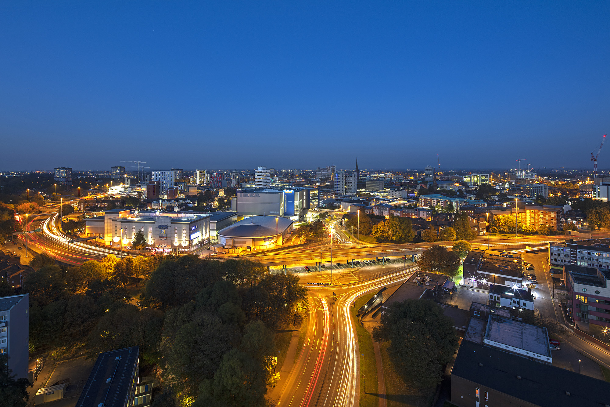 Image: A skyline showing trails of light around Coventry's ring road at night.