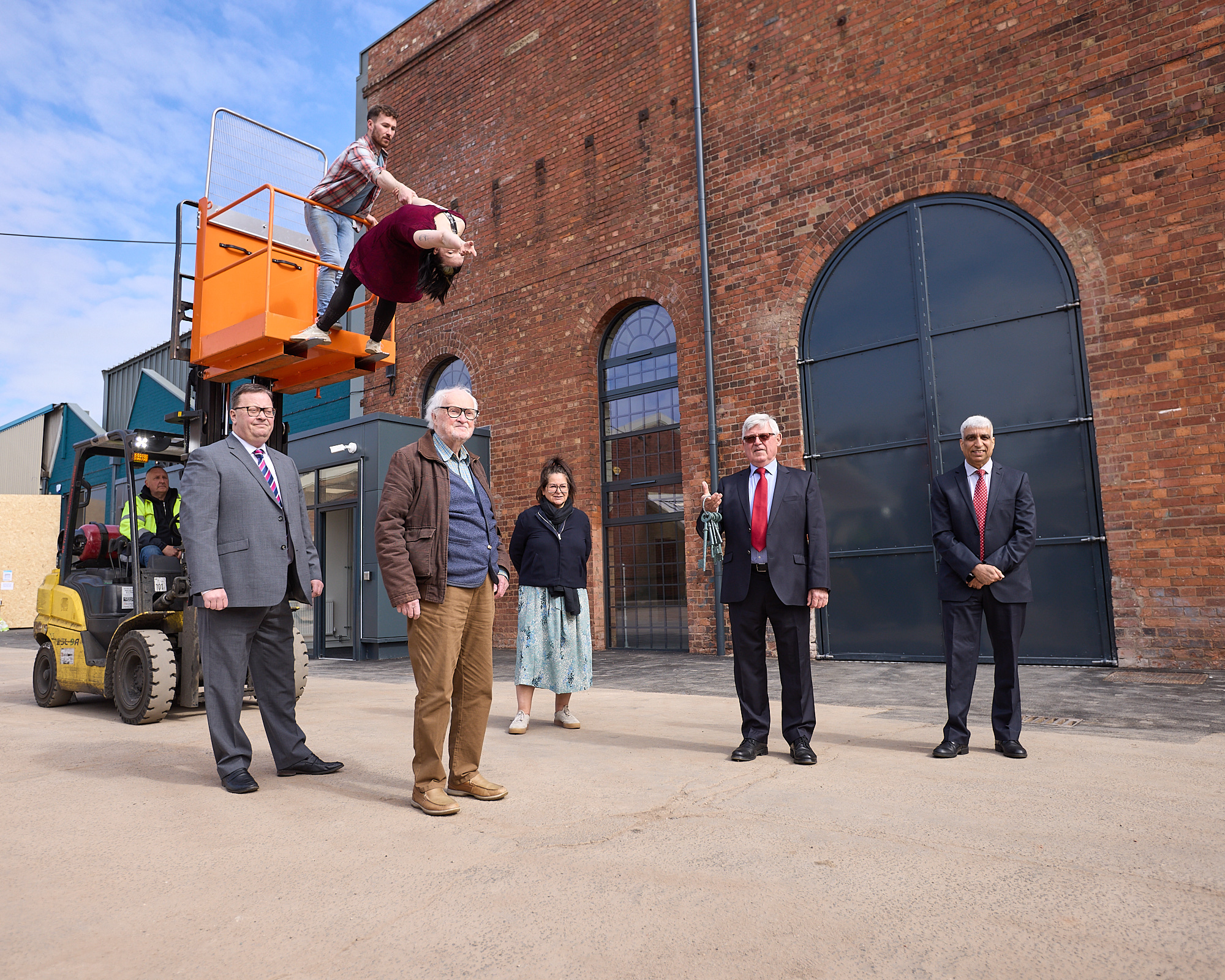 Aerialists Luka Owen and Daniel Connor perform with a fork lift truck. Standing in front of the truck are Roger Medwell, Chenine Bhathena, Robert Wigley, David Welsh and Zamurad Hussain